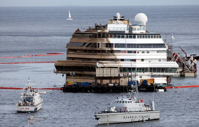 "The Costa Concordia is seen after it was lifted upright on the Tuscan Island of Giglio, Italy, early Tuesday morning, September 17, 2013. The crippled cruise ship was pulled completely upright early Tuesday after a complicated, 19-hour operation to wrench it from its side where it capsized last year off Tuscany, with officials declaring it a ""perfect"" end to a daring and unprecedented engineering feat. (Photo by Andrew Medichini/AP Photo)"