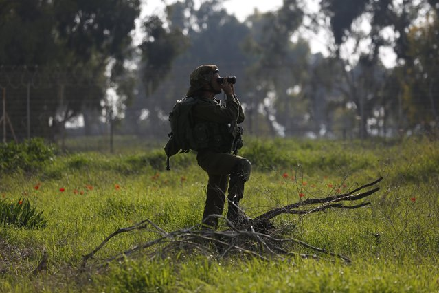 An Israeli soldier uses his binoculars as he looks towards the northern part of the Israeli Gaza border in southern Israel January 13, 2016. An Israeli aircraft attacked a group of Palestinians in the Gaza Strip on Wednesday who the military said planned to detonate a bomb at the border with Israel, and a Palestinian militant faction said one of its men was killed. (Photo by Amir Cohen/Reuters)