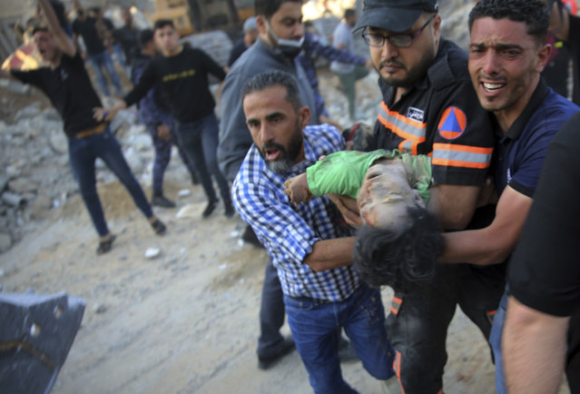 Palestinians carry the body of a child found in the rubble of a house belonging to the Al-Tanani family, that was destroyed in Israeli airstrikes in town of Beit Lahiya, northern Gaza Strip, Thursday, May 13, 2021. (Photo by Abdel Kareem Hana/AP Photo)