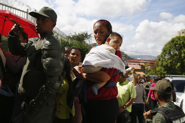 National Guards control access as people line up outside a state-run Bicentenario supermarket in Caracas, January 9, 2015. (Photo by Jorge Silva/Reuters)