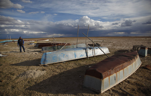 In this January 11, 2016 photo, a fisherman walks along the abandoned boats in the dried up Lake Poopo, on the outskirts of Untavi, Bolivia. The overturned fishing skiffs lie abandoned on the dried up former shores of what was Bolivia's second-largest lake. (Photo by Juan Karita/AP Photo)