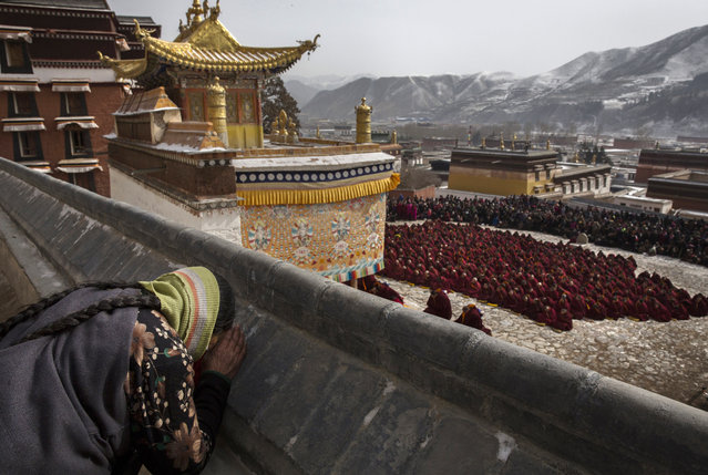 A Tibetan Buddhist woman bows her head in prayer as monks take part in a special prayer during Monlam or the Great Prayer rituals on March 5, 2015 at the Labrang Monastery, Xiahe County, Amdo, Tibetan Autonomous Prefecture, Gansu Province, China. (Photo by Kevin Frayer/Getty Images)