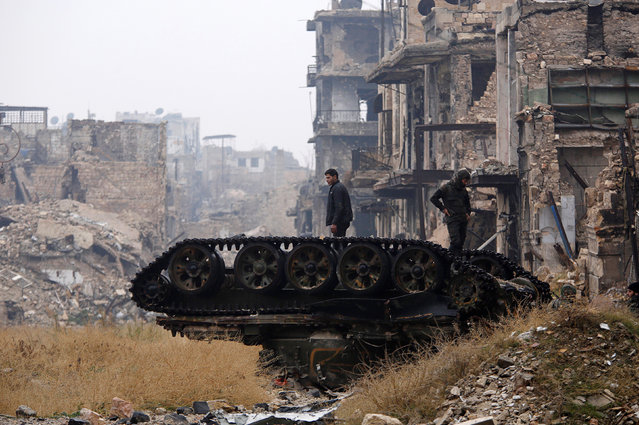 Forces loyal to Syria's President Bashar al-Assad stand atop a damaged tank near Umayyad mosque, in the government-controlled area of Aleppo, during a media tour, Syria December 13, 2016. (Photo by Omar Sanadiki/Reuters)