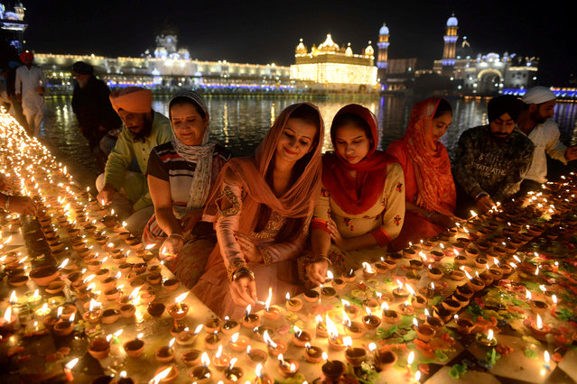 "Indian Sikh devotees light lights diyas (earthen lamps) during Bandi Chhor Divas or Diwali at the Golden Temple in Amritsar on November 7, 2018. Sikhs celebrate ""Bandi Chhor Divas"", also on the same day as the Hindu festival of Diwali, to mark the historic return of the sixth Guru, Guru Hargobind. (Photo by Narinder Nanu/AFP Photo)"