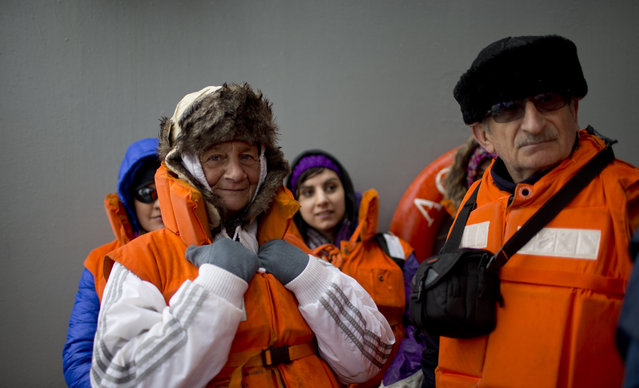 In this January 22, 2015 photo, Chilean tourists Estela Dorion, left, and Renato Valenzuela, wait on the deck of The Aquiles, a Chilean Navy icebreaker, for a zodiac that will transport them to the Bernardo O'Higgins scientific station, Antarctica. The harsh environment requires vacationers to come with many essentials: water-resistant hiking boots, several layers of winter clothes including long underwear and a parka, and powerful sun lotion and dark shades with extra ultraviolet protection. (Photo by Natacha Pisarenko/AP Photo)