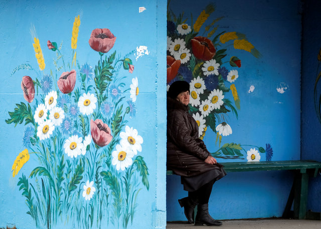 UKRAINE: A woman waits for a bus at a bus stop in the village of Khazhyn, Zhytomyr region, Ukraine November 11, 2016. (Photo by Gleb Garanich/Reuters)