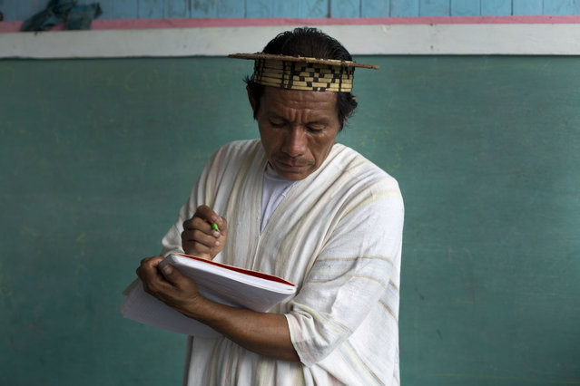 In this March 16, 2015 photo, Ashaninka Indian Gabriel Lopez, his community's only school teacher, writes down the names of people attending a weekly meeting in the hamlet of Saweto, Peru. Lopez is bilingual, speaking both Ashaninka and Spanish, like the majority of his community. However, Lopez teaches students in their native language. (Photo by Martin Mejia/AP Photo)