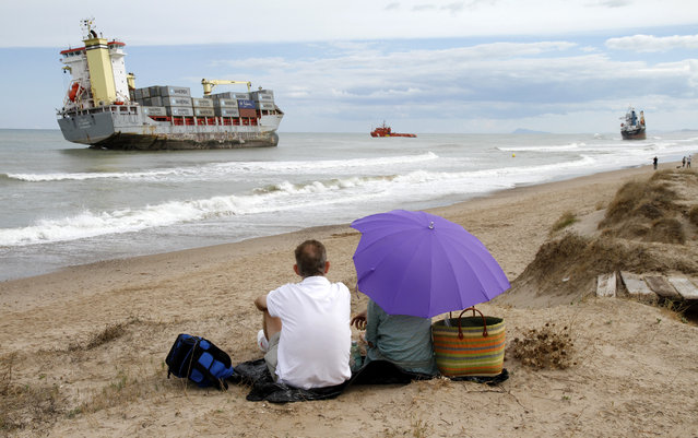 A couple sitting along the coast observe two cargo ships stranded close to the shore after a heavy rainstorm in Valencia, September 29, 2012. (Photo by Heino Kalis/Reuters)