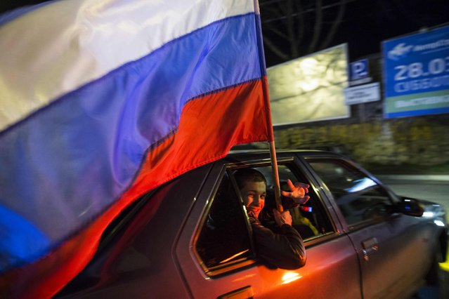 A man holding a Russian flag looks out of the car window during the celebrations for the first anniversary of the Crimean treaty signing in Sevastopol, March 18, 2015. (Photo by Maxim Shemetov/Reuters)
