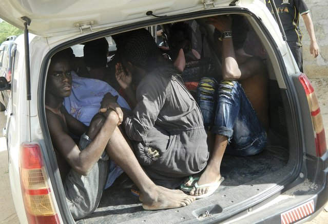 Students of the Garissa University College take shelter in a vehicle after fleeing from an attack by gunmen in Garissa, Kenya, Thursday, April 2, 2015. (Photo by AP Photo/Stringer)