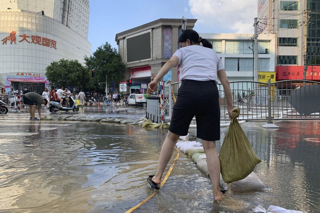 A woman moves a sandbag along a flooded road in the aftermath of the heaviest recorded rainfall in Zhengzhou in central China's Henan province on Saturday, July 24, 2021. Rescuers used bulldozers and rubber boats to move residents out of flooded neighborhoods in central China on Saturday after torrential rains killed at least 56 people. (Photo by Dake Kang/AP Photo)