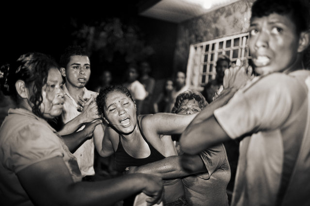 """""""Cries"""". Cries in the Sauce Colony of San Pedro Sula for a shot in the street. San Pedro Sula is the most violence city of the world. Photo location: San Pedro Sula, Honduras. (Photo and caption by Javier Arcenillas/National Geographic Photo Contest)"""