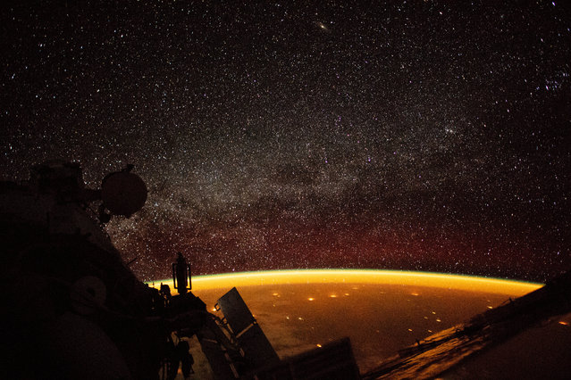"An orange hue envelops the Earth, known as ""airglow"", a phenomenon that occurs when ultraviolet radiation hits molecules in the atmosphere and creates a band of light that reaches 50 to 400 miles high, in this image taken on board the International Space Station (ISS), October 7, 2018. (Photo by NASA/Handout via Reuters)"