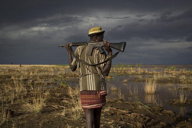 An armed Turkana man walks towards the shores of Lake Turkana near a temporary fishing camp some kilometres from Todonyang near the Kenya-Ethiopia border in northwestern Kenya October 12, 2013. (Photo by Siegfried Modola/Reuters)