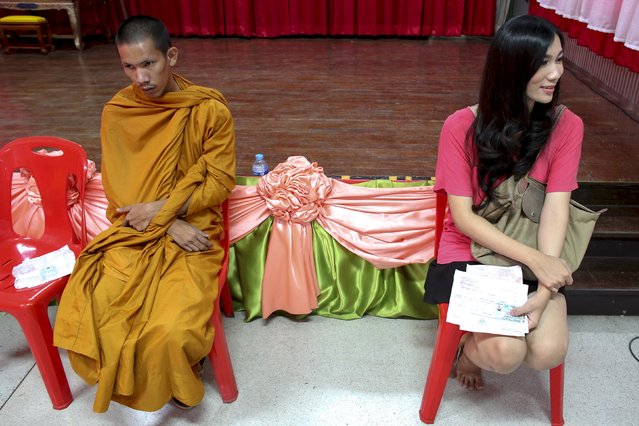 Nopparat (R), a 24-year-old transgender, and a Buddhist monk (L) wait to speak to officers during an army draft held at a school in Bang Na in Bangkok April 3, 2015. Thai men over 21 must serve in the army. Those who volunteer serve six months, but others choose the annual lottery, which goes on for 10 days in recruitment centres around Thailand. Only those not considered physically capable of service, the mentally ill and those who have significantly altered their physical appearance, such as transgenders, are exempt. Picture taken April 3, 2015. (Photo by Athit Perawongmetha/Reuters)