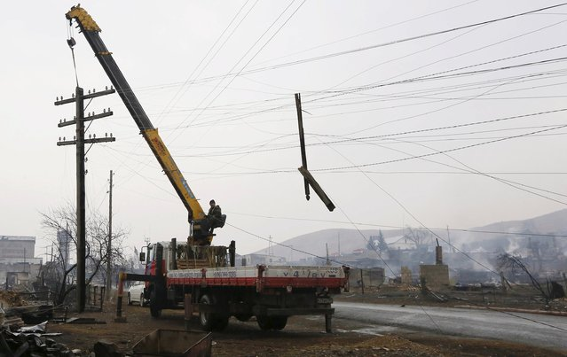 A worker operates a mobile crane while lifting a burnt electric line mast in the settlement of Shyra, damaged by recent wildfires, in Khakassia region, April 13, 2015. (Photo by Ilya Naymushin/Reuters)