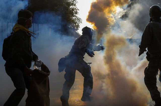 An anti-government protester throws a tear gas canister towards policemen during clashes at the Thai-Japan youth stadium in Bangkok, on December 26, 2013. (Photo by Athit Perawongmetha/Reuters)