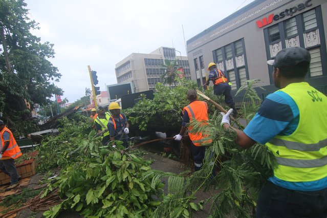 Workers clear a damaged tree from the center of Fiji's capital Suva in the aftermath of Cyclone Winston, February 21, 2016. Downed power lines and flooding are hampering relief efforts in Fiji after one of the most powerful storms recorded in the southern hemisphere tore through the Pacific island nation, flattening remote villages and killing at least five people. (Photo by Steven Saphore/Reuters)