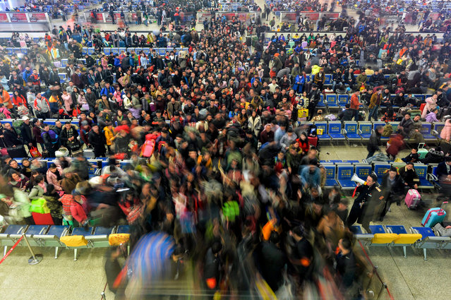 A long exposure photo made available on 13 January 2017 shows passengers flowing to their train at Hankou Railway Station in Wuhan, Hubei Province, central China, late 12 January 2017, immediately before the first day of the 40-day Spring Festival Travel Peak. China expects to carry some three billion trips during the 40 days. (Photo by EPA/Stringer)
