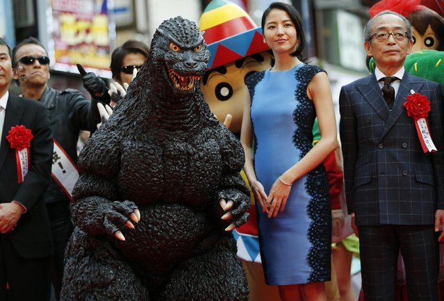 Godzilla and actress Masami Nagasawa, second right, attend a ceremony in downtown Tokyo for the opening of an entertainment complex run by its studio, Toho, where Godzilla head is on display, Thursday, April 16, 2015. The irradiated monster was appointed special resident and tourism ambassador for this Shinjuku ward, known for its down-home bars and noodle restaurants. (Photo by Shuji Kajiyama/AP Photo)