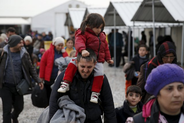 A migrant carries a child on his shoulders as migrants are returned from a train to a camp near the Macedonian-Greek border in Gevgelija, Macedonia, February 24, 2016. The train was stopped from leaving north after the transit camp on the country's northern border with Serbia filled up with migrants who had been denied entry into Serbia. (Photo by Marko Djurica/Reuters)