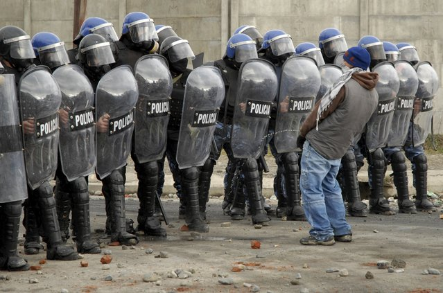 A protester urinates in front of a row of policemen during riots following the death of a 15-year-old boy in San Carlos de Bariloche, in this June 18, 2010 file photo. (Photo by Alejandra Bartoliche/Reuters)