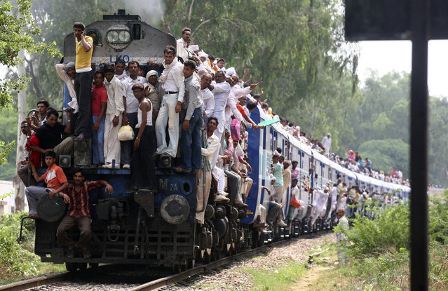 Hindu devotees travel in an overcrowded passenger train after taking a holy dip and offering prayers in the waters of Brahma Sarovar, July 22, 2009. (Photo by Ajay Verma/Reuters)