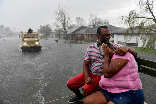 """People react as a sudden rain shower soaks them with water while riding out of a flooded neighborhood in a volunteer high water truck assisting people evacuating from homes after neighborhoods flooded in LaPlace, Louisiana on August 30, 2021 in the aftermath of Hurricane Ida. Rescuers on Monday combed through the """"catastrophic"""" damage Hurricane Ida did to Louisiana, a day after the fierce storm killed at least two people, stranded others in rising floodwaters and sheared the roofs off homes. (Photo by Patrick T. Fallon/AFP Photo)"""