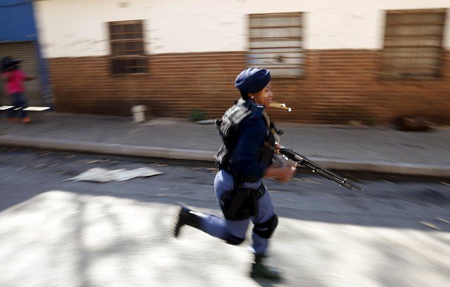 A police officer runs while dispersing African immigrants who are carrying machetes in Johannesburg, April 17, 2015. (Photo by Siphiwe Sibeko/Reuters)