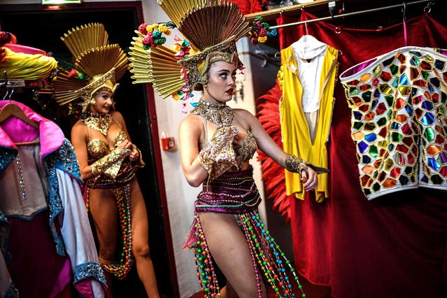 Dancers wait in the wings before performing in a full-dress rehearsal at the Moulin Rouge in Paris on September 8, 2021, two days ahead of the reopening of the cabaret following an 18-month closure amid the COVID-19 pandemic. Closed for a year and a half due to the pandemic, the Moulin Rouge and Le Lido, emblems of the crazy Parisian nights since 1889, are finally reopening. (Photo by Christophe Archambault/AFP Photo)
