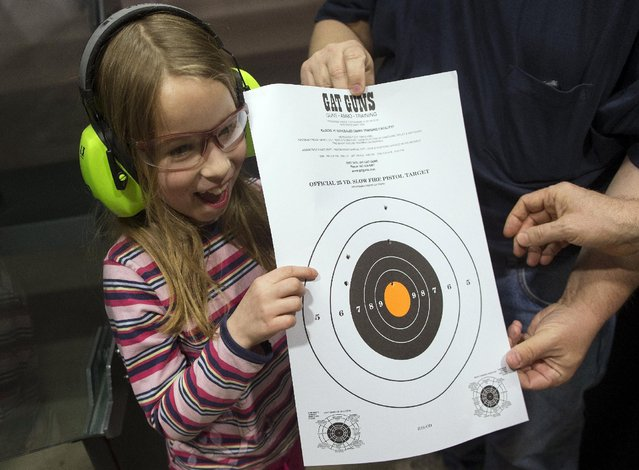 Joanna Zuber reacts to her results from shooting at a target during a Youth Handgun Safety Class at GAT Guns in East Dundee, Illinois, April 21, 2015. The class is geared toward children aged 7 to 14 to teach them firearms safety and how to properly fire a handgun. (Photo by Jim Young/Reuters)