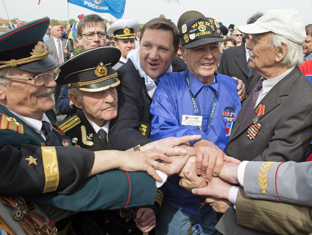 Russian veterans Victor Maximov, right, and Nikolai Mihalovic Beljajev, second left, hold hands with US veteran Chet Yastrzemski of Southhampton, New York, second right, and others during the 70th anniversary celebrations of the so-called Elbe Day in Torgau, eastern Germany, Saturday, April 25, 2015. (Photo by Jens Meyer/AP Photo)