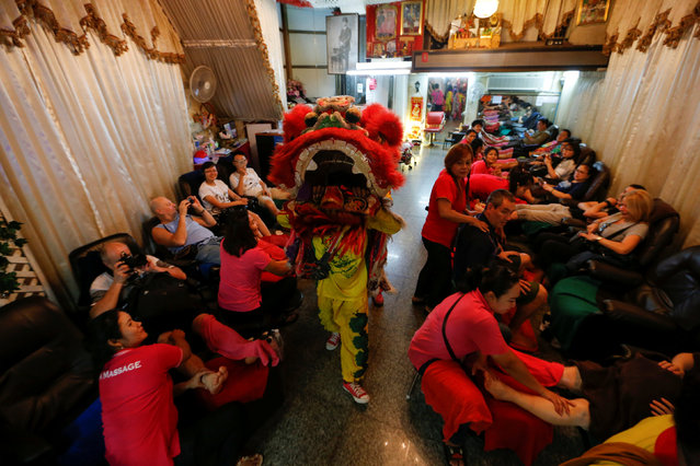 A Chinese lion dances inside a massage shop during the Lunar New Year's eve celebration in Chinatown, in Bangkok, Thailand January 27, 2017. (Photo by Jorge Silva/Reuters)