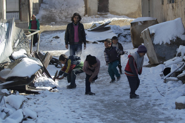 Children play with snow near rubble of damaged buildings in al-Rai town, northern Aleppo countryside, Syria January 28, 2017. (Photo by Khalil Ashawi/Reuters)