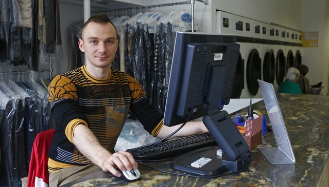 "Roman Bazulchuk, 25, poses for a photograph at his workplace, Aqua Cleaning, in the London constituency of Brent Central, Britain, April 13, 2015. Bazulchuk was born in Ukraine and said: ""Cameron is too tough on cuts, but I believe he is a stronger leader than Milliband"". (Photo by Eddie Keogh/Reuters)"