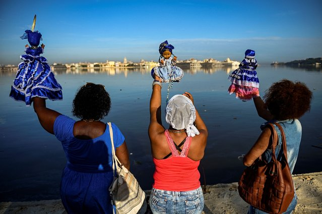 Followers of the Yoruba sea goddess Yemaya, give offering at the Havana harbour during Yemaya Day celebrations in Havana, on September 7, 2021. (Photo by Yamil Lage/AFP Photo)