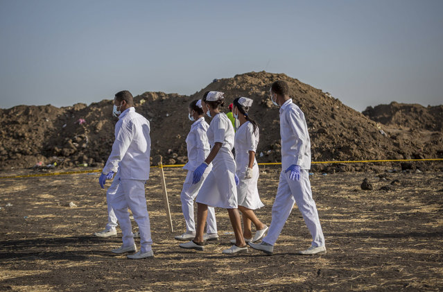 Nurses walk to collect materials, under the instruction of investigators, at the scene where the Ethiopian Airlines Boeing 737 Max 8 crashed shortly after takeoff on Sunday killing all 157 on board, near Bishoftu, or Debre Zeit, south of Addis Ababa, in Ethiopia Tuesday, March 12, 2019. (Photo by Mulugeta Ayene/AP Photo)