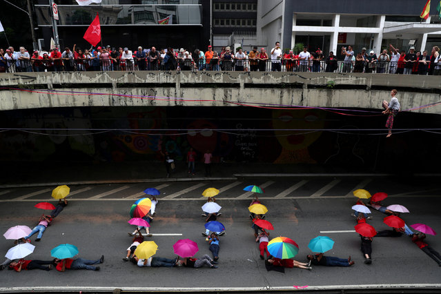 """Supporters of Brazil's former president Luiz Inacio Lula da Silvawrite """"LULA"""" during a performance as they protest to demand Lula's freedom on the one-year anniversary of his arrest, in Sao Paulo, Brazil, April 7, 2019. (Photo by Amanda Perobelli/Reuters)"""