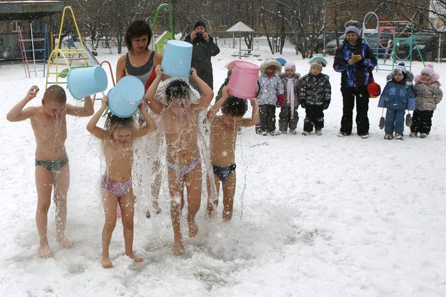 Children watch their classmates pour cold water on themselves under the watch of fitness coach Oksana Kabochko (C) at local kindergarten number 317 during a snowfall in Russia's Siberian city of Krasnoyarsk, on February 20, 2014. (Photo by Ilya Naymushin/Reuters)