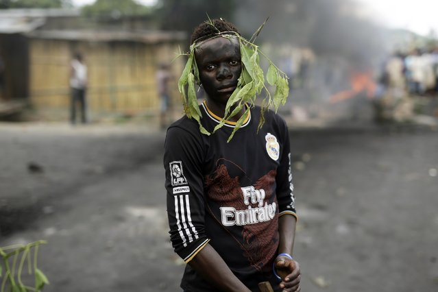 A demonstrator faces police  in the Musaga district of  Bujumbura, Burundi, Tuesday May 5, 2015. The Constitutional court validated  President Pierre Nkurunziza's decision to seek a third term, amid violent street protests. (Photo by Jerome Delay/AP Photo)