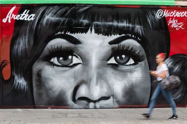 A woman walks past new street art in Shoreditch, east London, UK on August 19, 2018, paying tribute to the singer, Aretha Franklin who has died following a battle with pancreatic cancer. The mural has been created by artist, Jules Muck in collaboration with Global Street Art. (Photo by Vickie Flores/LNP)