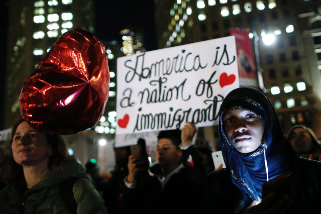Demonstrators hold signs as the New York Immigration Coalition holds a rally and protest against US Presidents Donald Trump' s immigration policies in Foley Square in New York on February 14, 2017. (Photo by Eduardo Munoz Alvarez/AFP Photo)