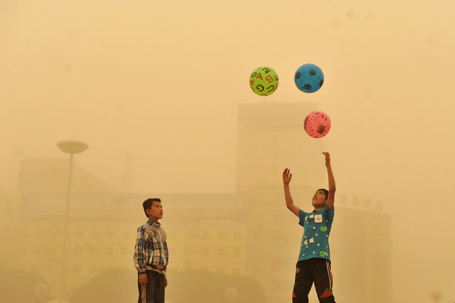 A boy watches as another boy play with balls, during a sandstorm in Kashgar city in northwestern China's Xinjiang Uighur Autonomous Region, Sunday, May 10, 2015. (Photo by Chinatopix Via AP Photo)