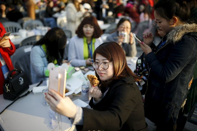 A Chinese tourist takes a selfie with a piece of fried chicken during an event organized by a Chinese company at a park in Incheon, South Korea, March 28, 2016. (Photo by Kim Hong-Ji/Reuters)