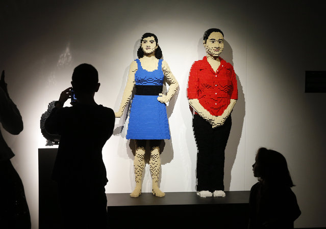 "Visitors take photo of ""Crow, Girl, Woman"", a Lego sculpture by U.S. artist Nathan Sawaya presented during an exhibition The Art of the Brick, in Paris, France, Thursday May 14, 2015. (Photo by Christophe Ena/AP Photo)"