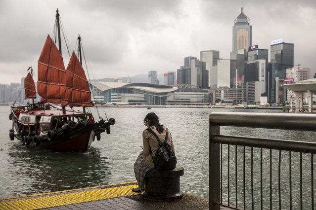 A junk boat sails in to dock as a woman sits on the pier in the central district of Hong Kong on May 15, 2019. (Photo by Isaac Lawrence/AFP Photo)