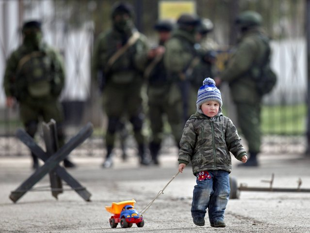 A child drags a toy truck past pro-Russian soldiers standing outside an Ukrainian military base in Perevalne, Crimea, Thursday, March 20, 2014. With thousands of Ukrainian soldiers and sailors trapped on military bases, surrounded by heavily armed Russian forces and pro-Russia militia, the Kiev government said it was drawing up plans to evacuate its outnumbered troops from Crimea back to the mainland and would seek U.N. support to turn the peninsula into a demilitarized zone.(Photo by Vadim Ghirda/AP Photo)