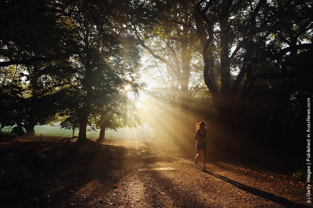 A woman runs through the early morning mist on Hampstead Heath
