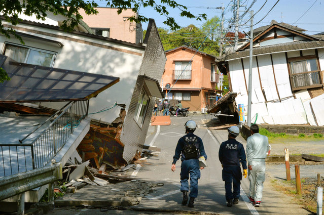 Riot policemen examine the damage of houses collapsed by a magnitude-6.5 earthquake in Mashiki, Kumamoto prefecture, southern Japan, Friday, April 15, 2016. (Photo by Shingo Nishizume/Kyodo News via AP Photo)