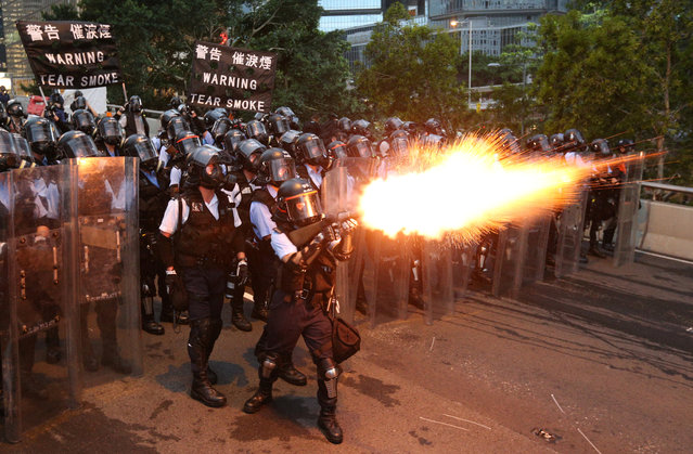 Police officers fire a tear gas during a demonstration against a proposed extradition bill in Hong Kong, China on June 12, 2019. (Photo by Athit Perawongmetha/Reuters)